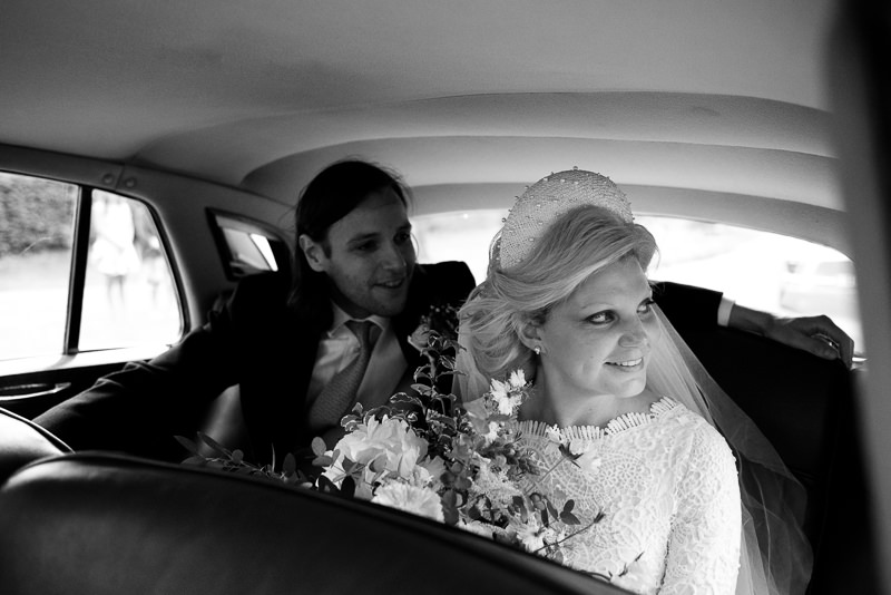 Bride and groom in back of car on their way to Walkern Hall