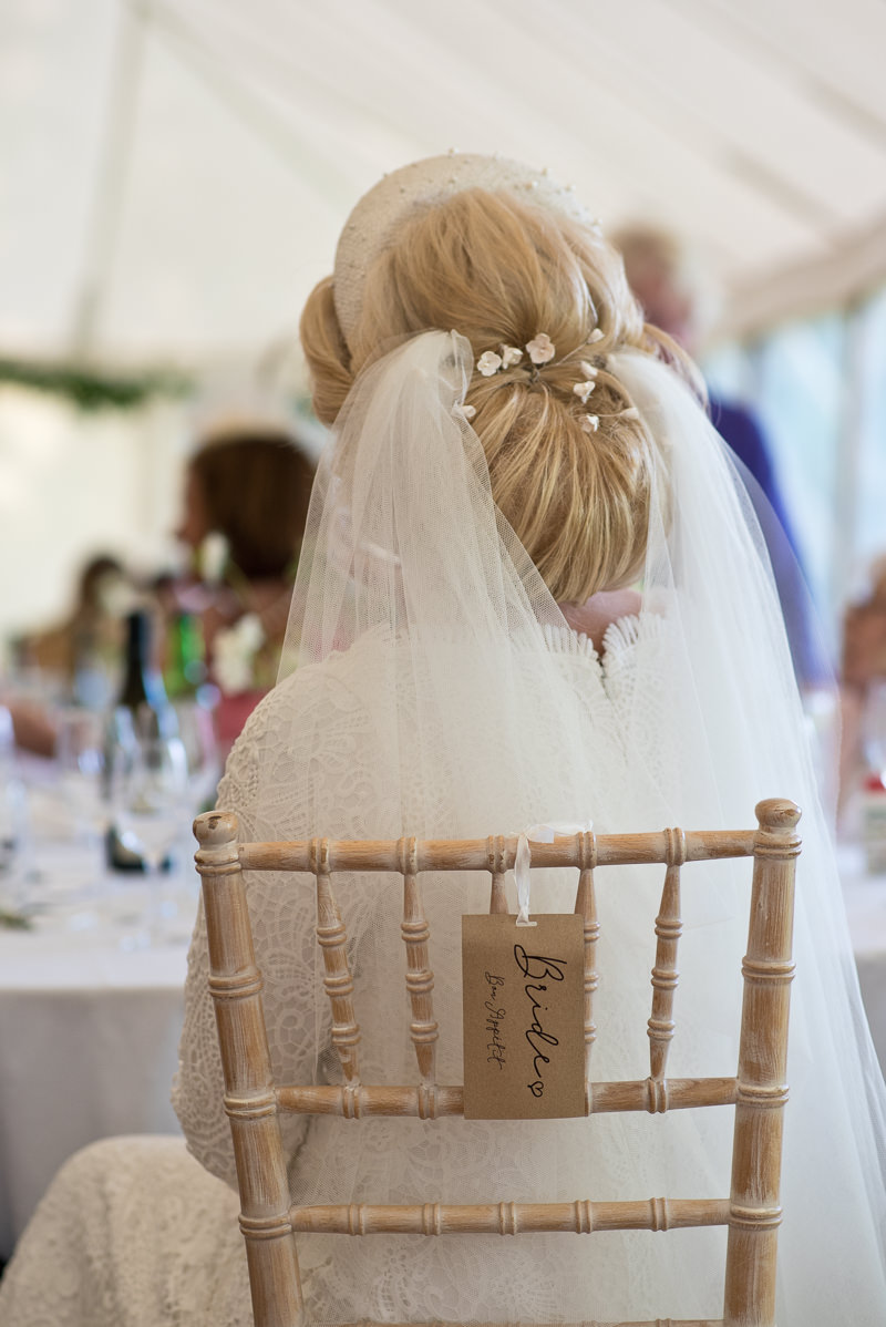 Bride with veil on chair labelled Bride