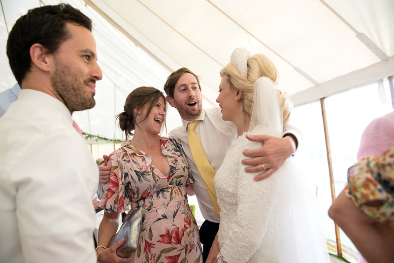 Bride mingles with guests at marquee wedding at Walkern Hall