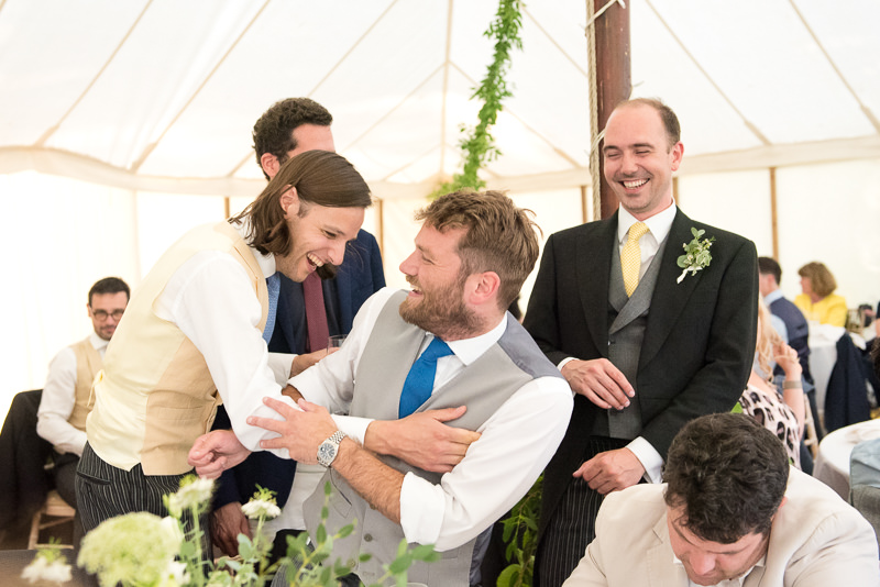 Groom laughs with guests in marquee at Walkern Hall