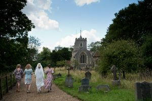 Bride arrives with bridesmaids at St Peter's Church in Benington