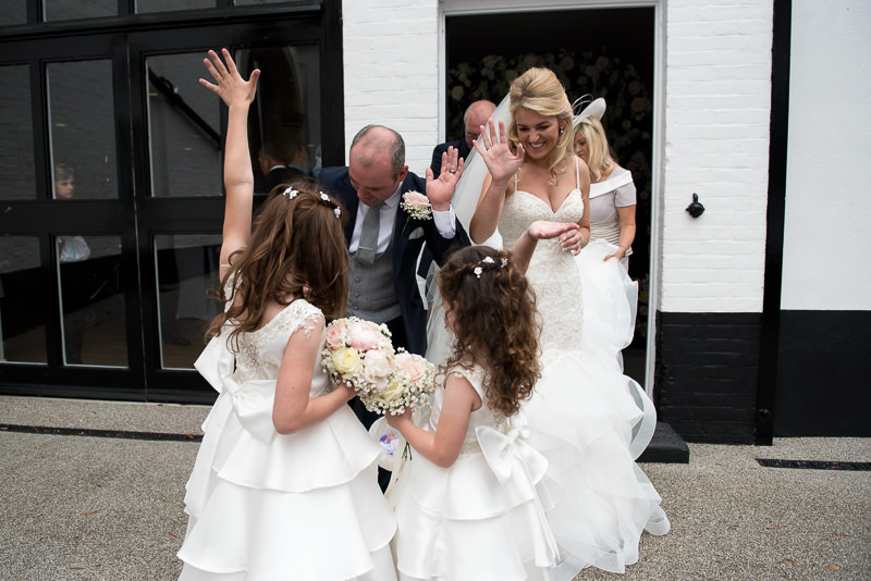 Bride and groom high five daughters after Boreham House wedding ceremony