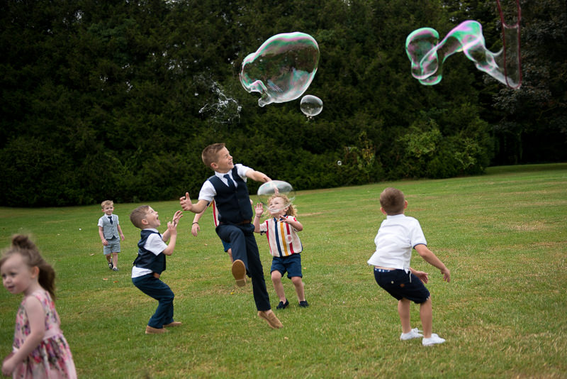 Children play with bubbles at Boreham House wedding