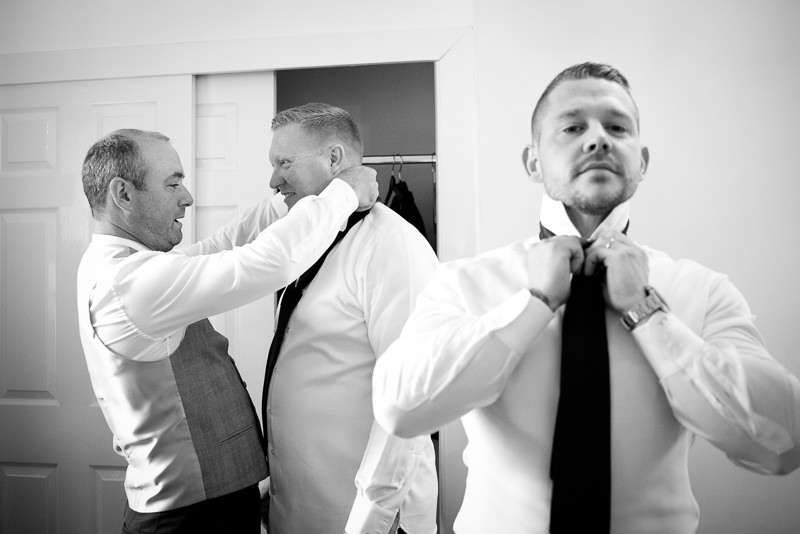 Groom getting ready at cottage in Boreham House