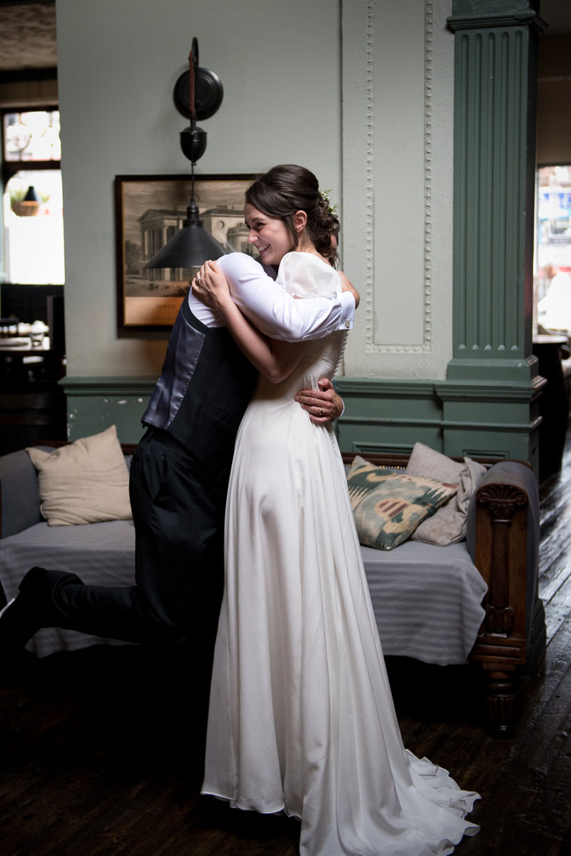 Bride and groom hug at wedding reception at Bull and Gate Kentish Town