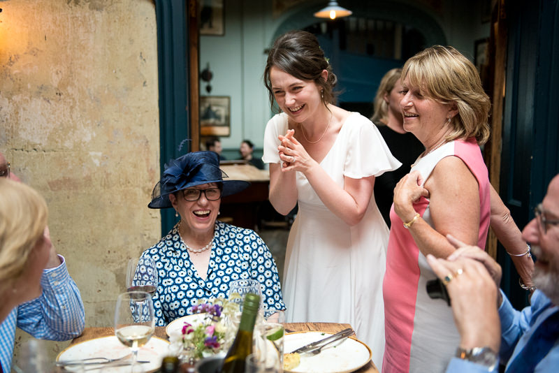 Bride laughs with guest during pub wedding reception at Bull and Gate Kentish Town