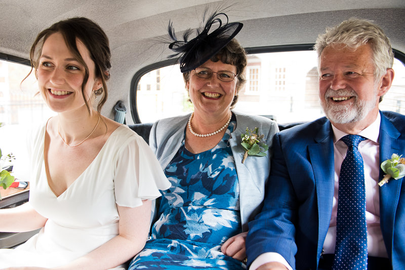 Bride in taxi with parents