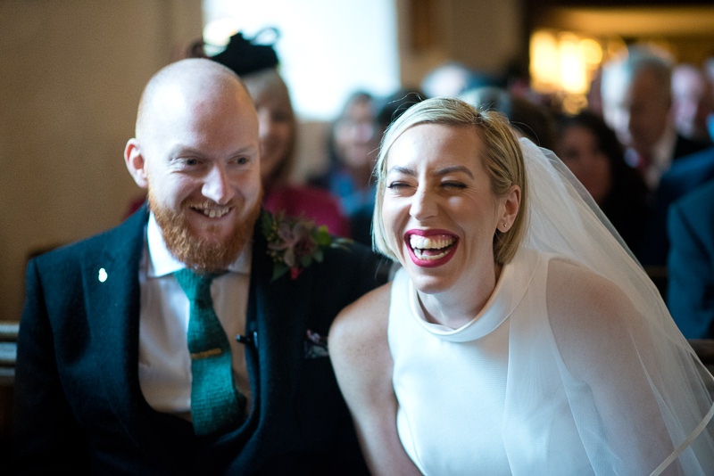 Bride giggles during wedding ceremony at Church of St James the Less
