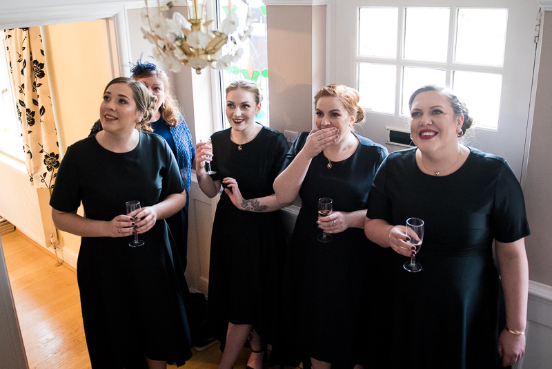 Bridesmaids dressed in black reacting to seeing bride for the first time